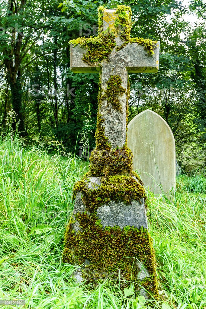 Stone graveside cross in cemetery covered in moss stock photo