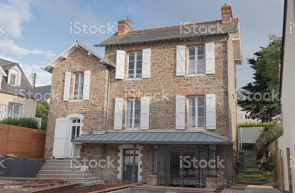 Stone house in Brittany with work on wooden terrace stock photo