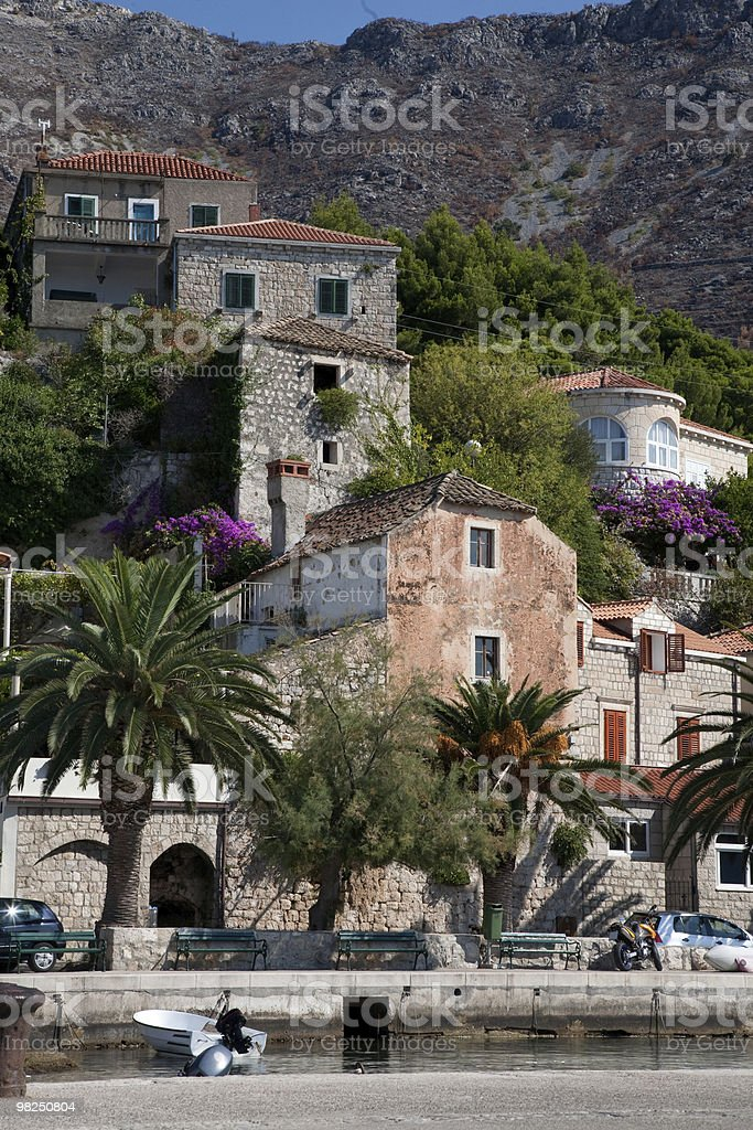 Stone houses with red ceramic tiles on Croatian shoreline. stock photo