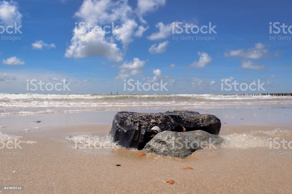 Stone in the sand at the beach stock photo
