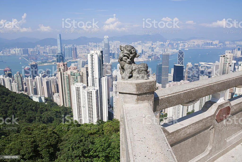 Stone lion statue with Hong Kong skyline in background royalty-free stock photo