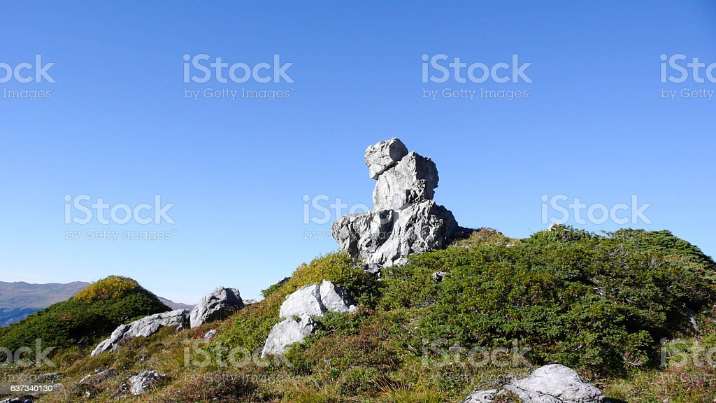 stone man on a summit in the Alps stock photo