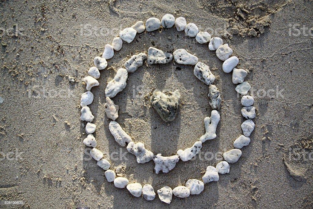 Stone mandala on the sand of beach stock photo