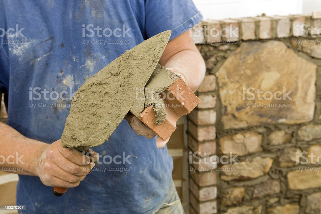 Stone Mason Buttering  Brick with Mortar for New Fireplace Surround stock photo
