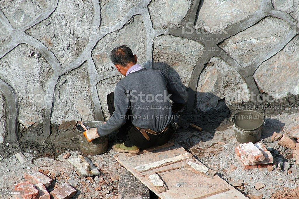 Stone Mason cementare un nuovo muro foto stock royalty-free