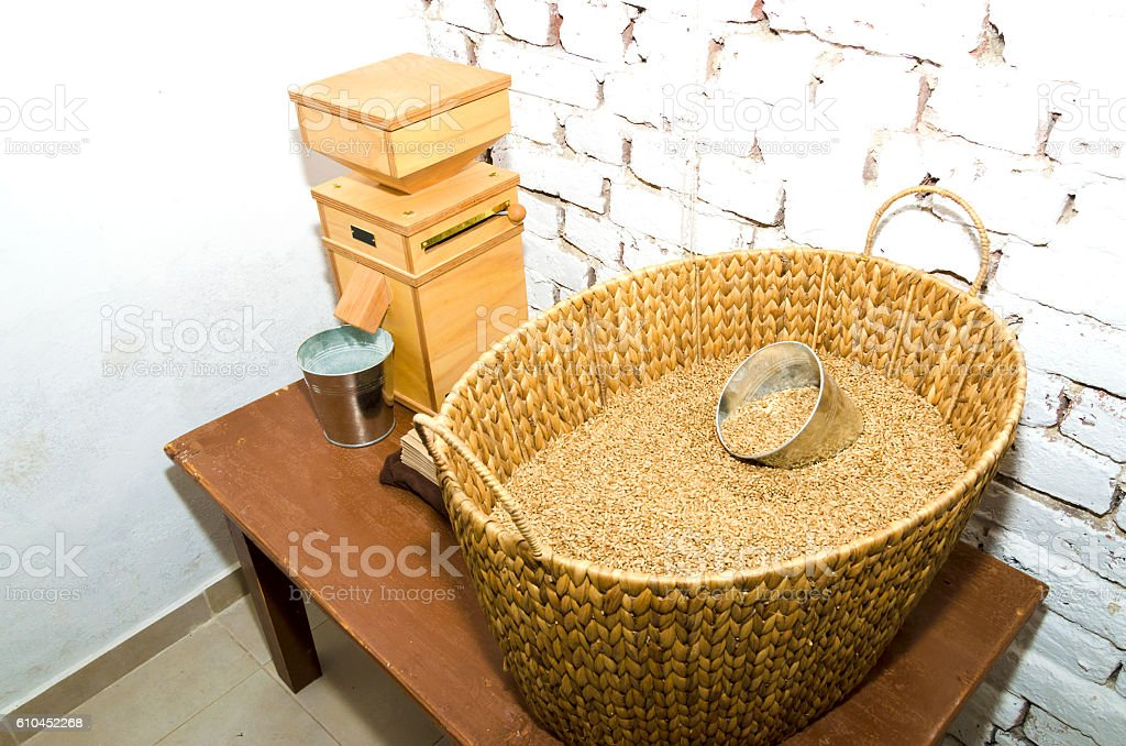 Stone mill and wicker basket in a small bakery stock photo