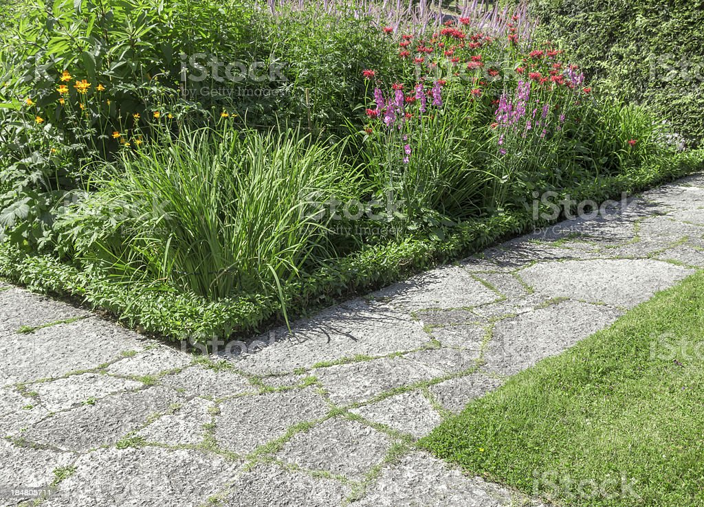 Stone paths in a sunny garden royalty-free stock photo
