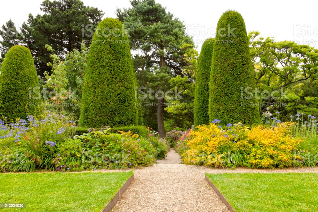 Stone pathway crossing summer flowers flowerbeds and lawn in a landscaped garden, with pine trees and shaped conifers stock photo