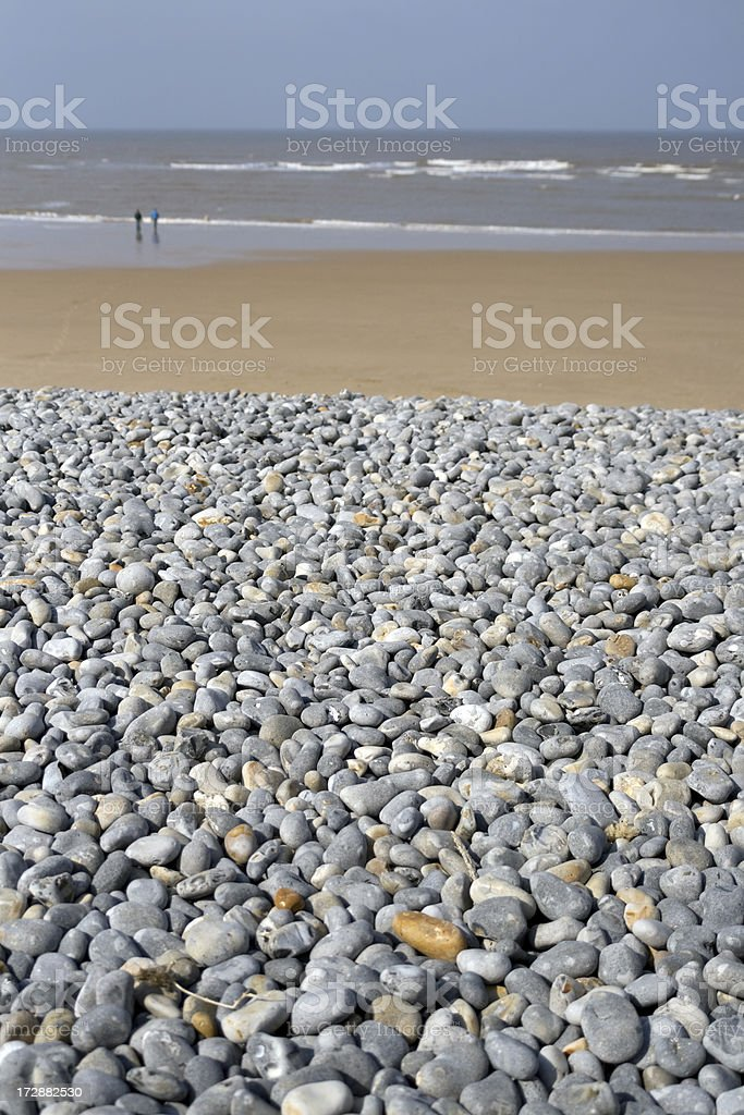 Stone pebbles on a beach, with people walking royalty-free stock photo