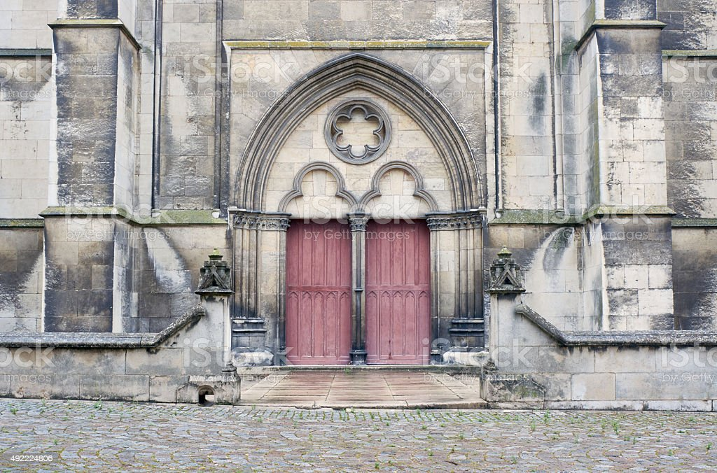 Stone portal and a wooden door to the medieval church stock photo