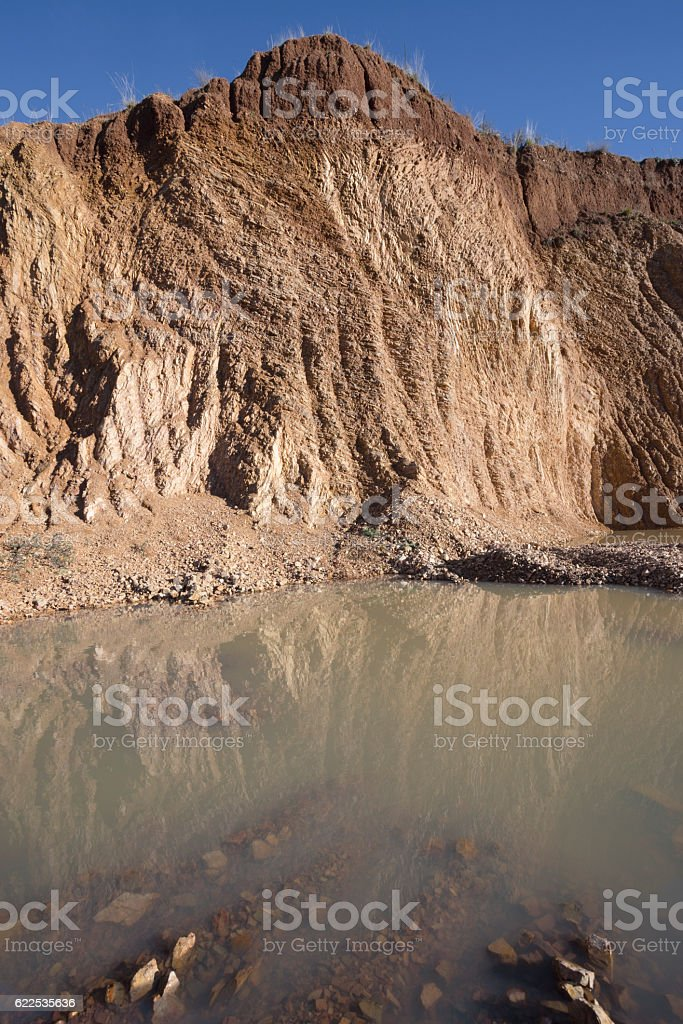 Stone quarry hill mine with large puddle in the bottom stock photo