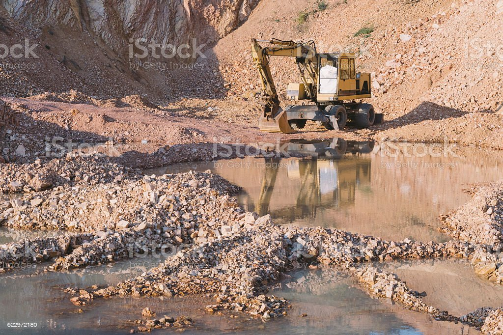 Stone quarry mine with large puddles and bagger stock photo