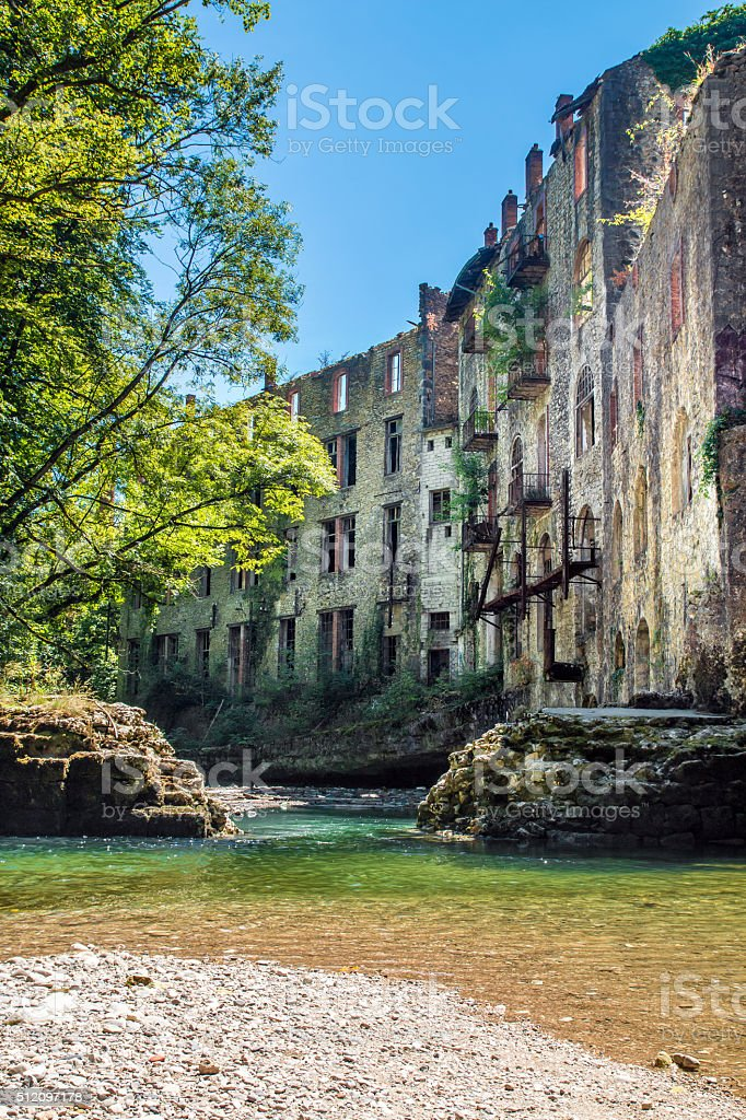 Stone ruins of old factory along river in french forest stock photo