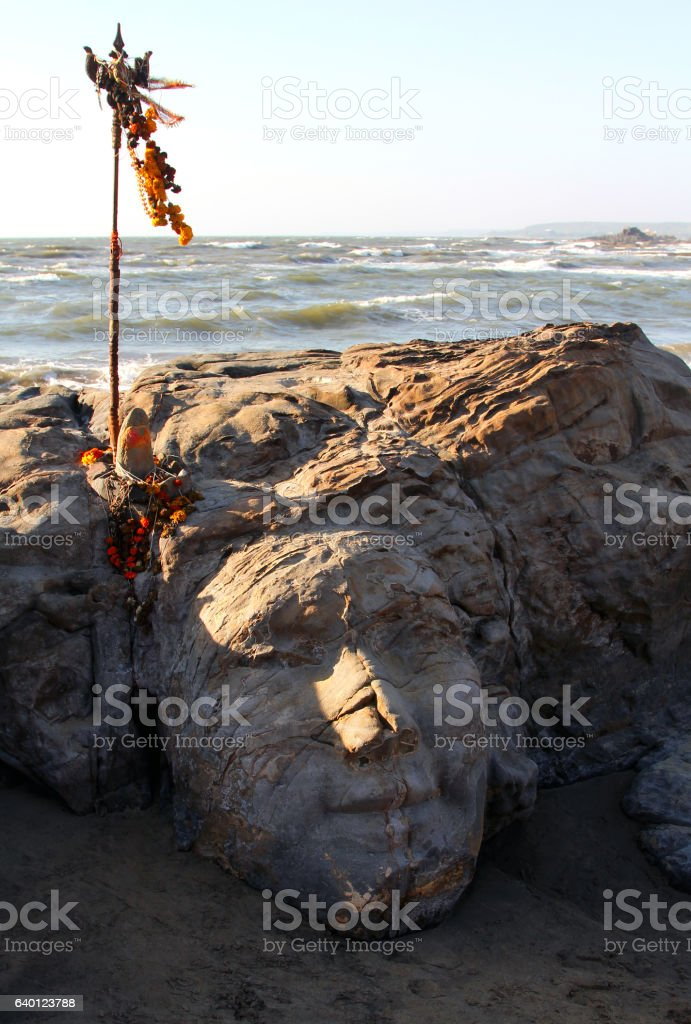 stone Shiva face on Vagator beach of Goa, India stock photo