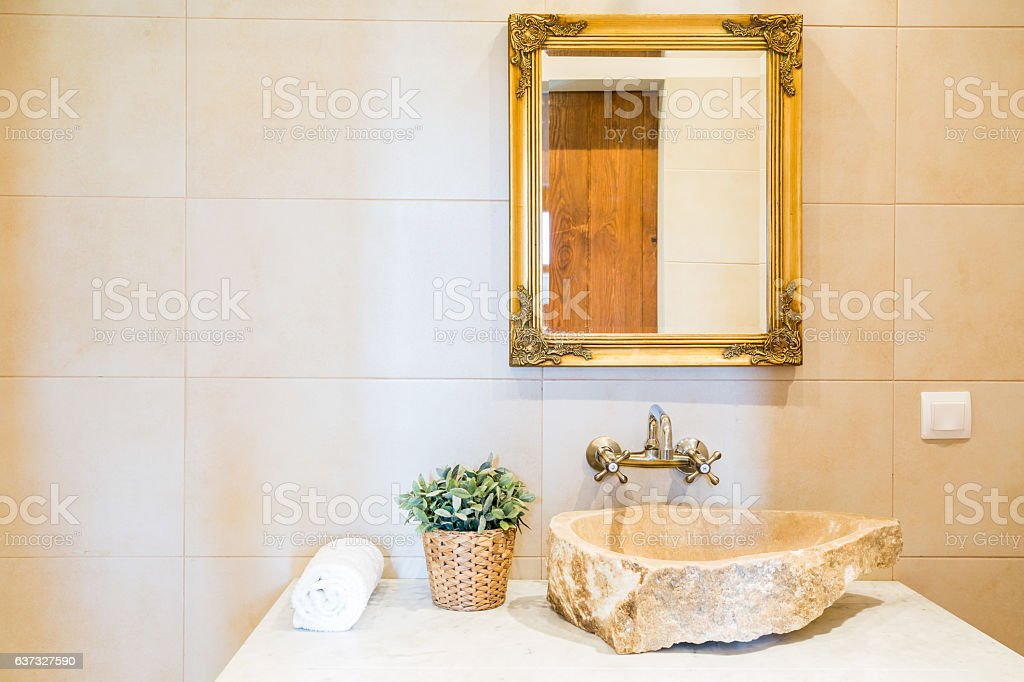 Stone sink and mirror in bathroom stock photo