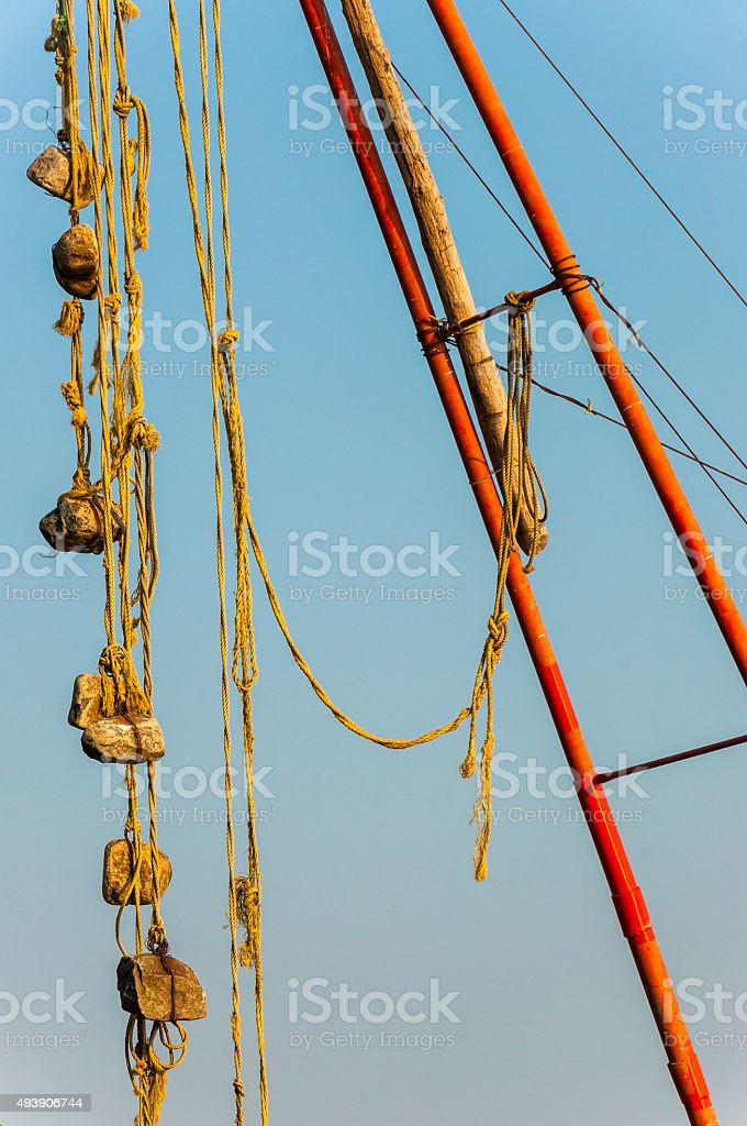 Stone sinkers hanging on the Chinese fishing nets stock photo