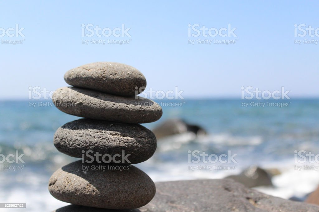 Stone Stacking on the Beach with Waves Breaking in the Background stock photo