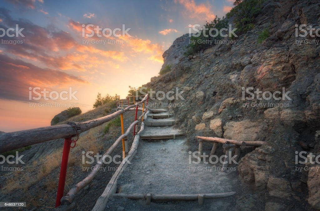 Stone stairs with wooden railing in the mountains at sunset. Landscape with mountain path and rocks against colorful blue sky with clouds. Trail leading to the mountain peak. Adventure and travel stock photo