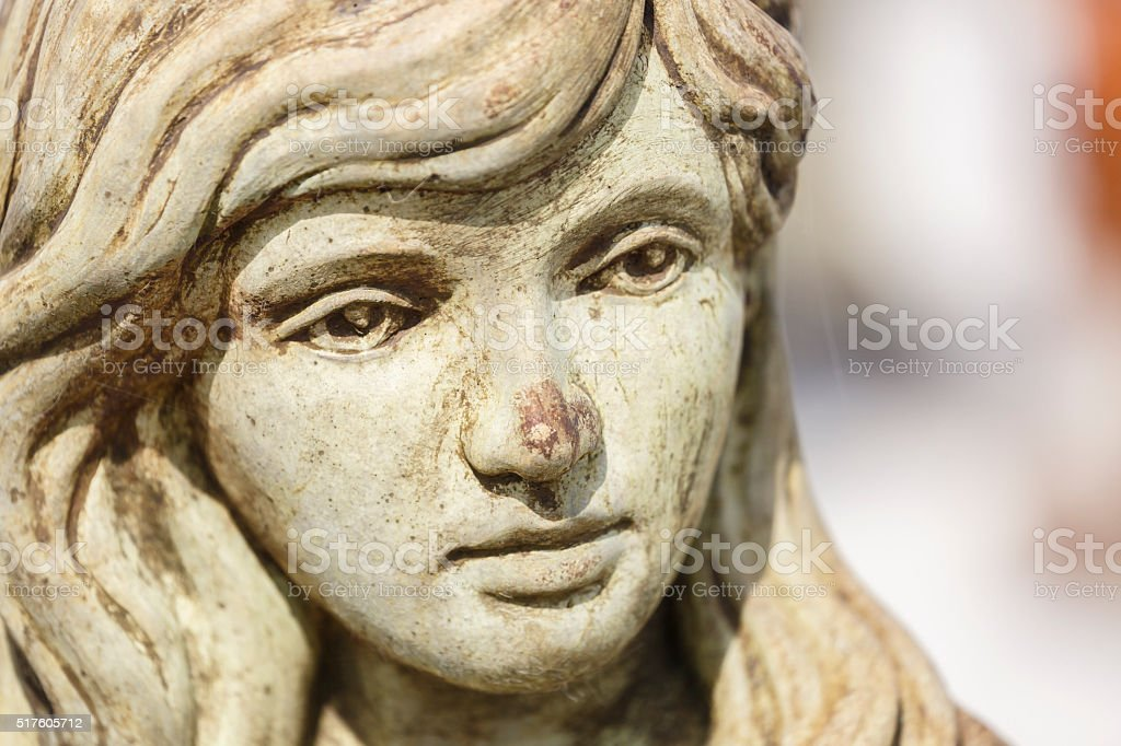 Stone Statue of a Little Girl's Face In Public Graveyard stock photo