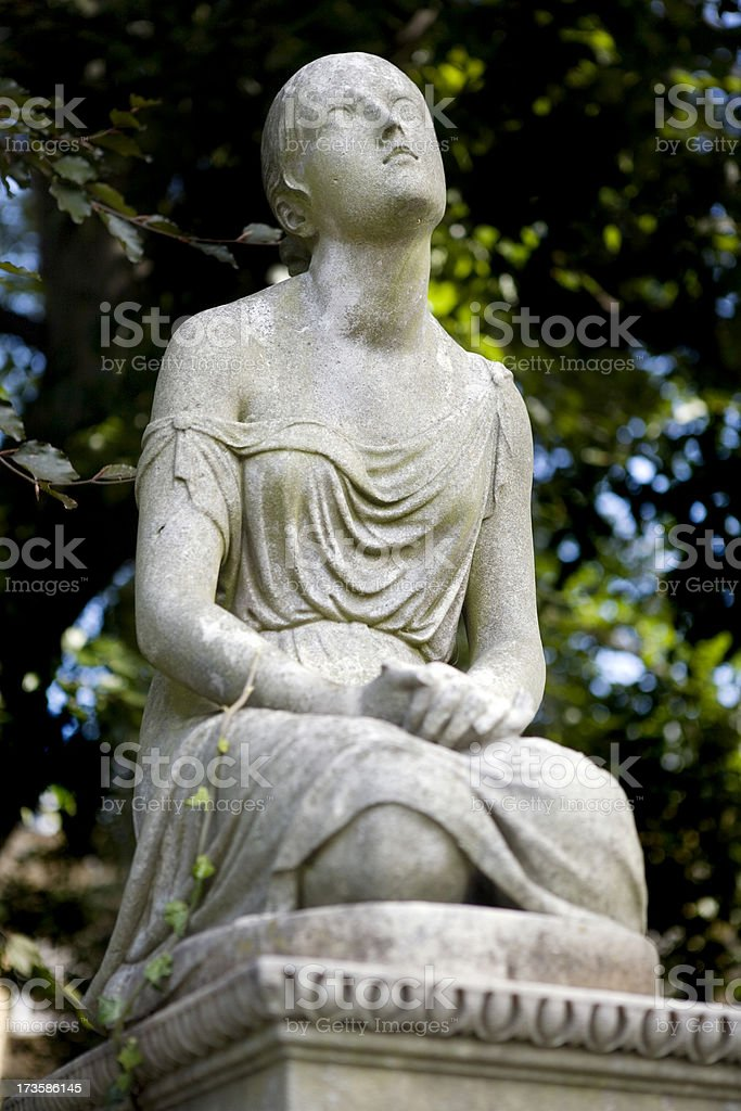 Stone Statue on Grave in Old Cemetery stock photo