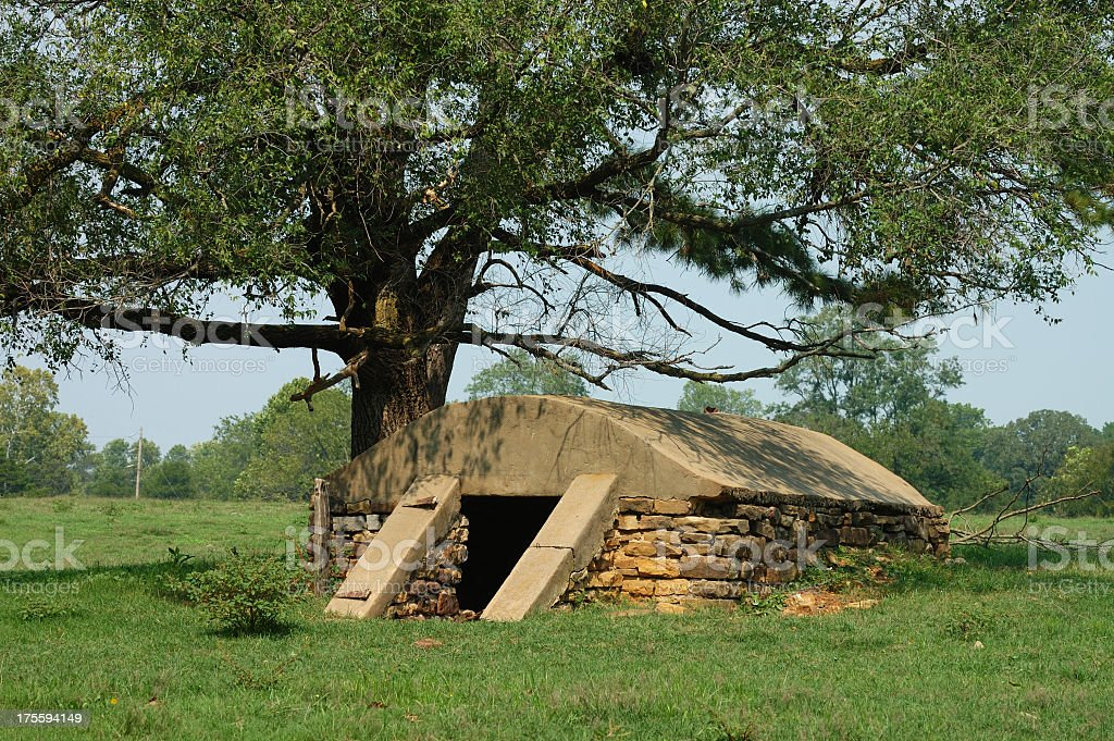 Stone storm shelter under a tree on a sunny day stock photo