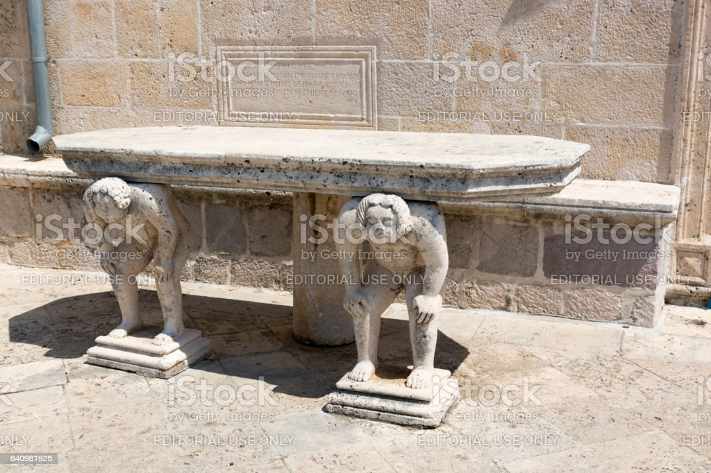 Stone table with male figures near the church on the island of Gospa od Skrpela in the Boko-Kotorsky Gulf. Montenegro. stock photo