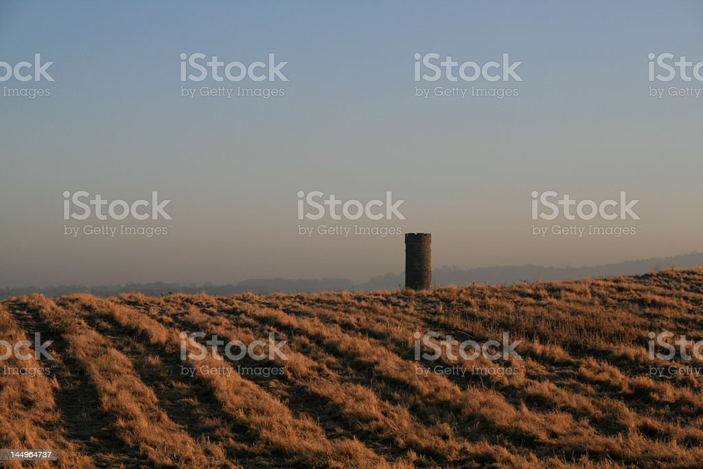 Stone tower in a wintery field stock photo