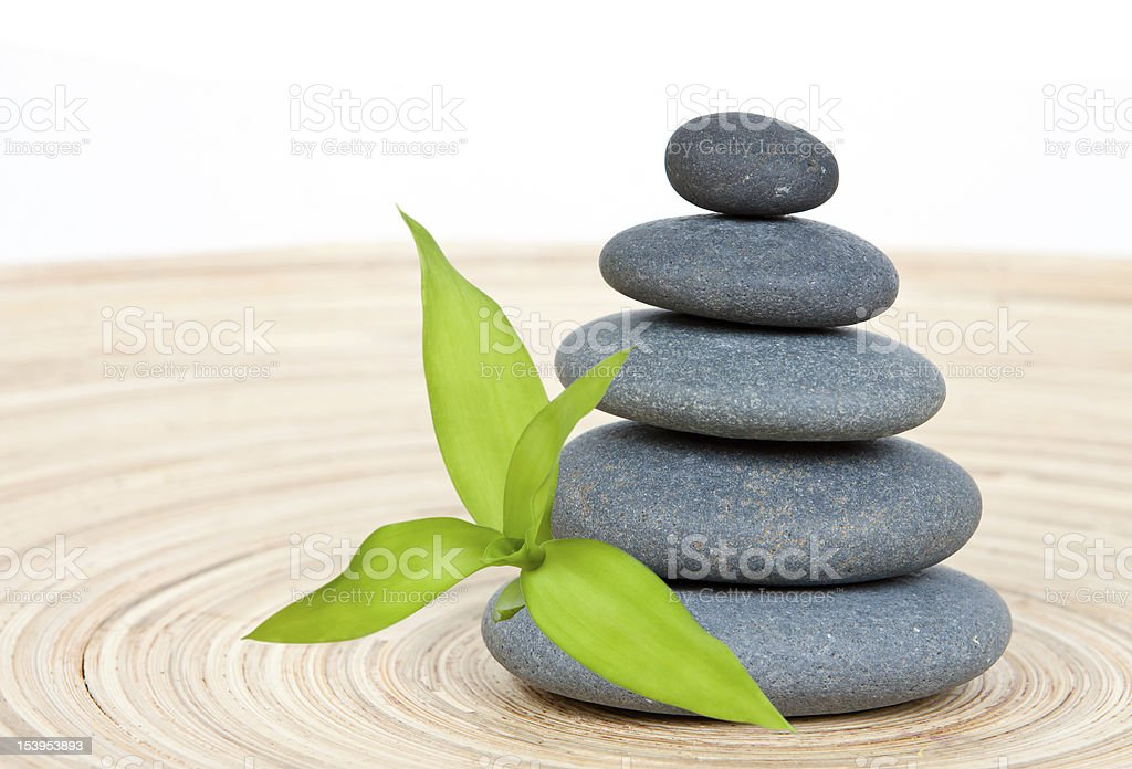 Stone tower on a wooden board with green bamboo leaf stock photo