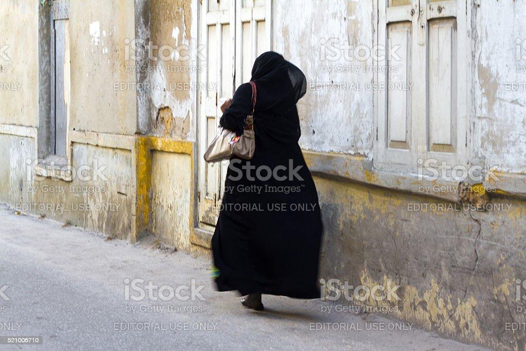 Stone Town, Zanzibar: Woman in Black Chador Hurrying stock photo