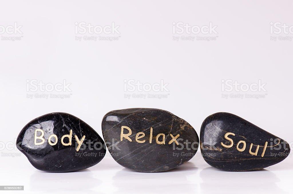 Stone treatment. Black massaging stones isolated on a white background. stock photo
