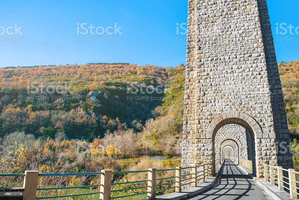 Stone viaduct arch architecture with mountains in autumn in France stock photo