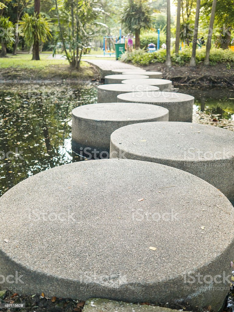 Stone walkway across the river in the park. royalty-free stock photo