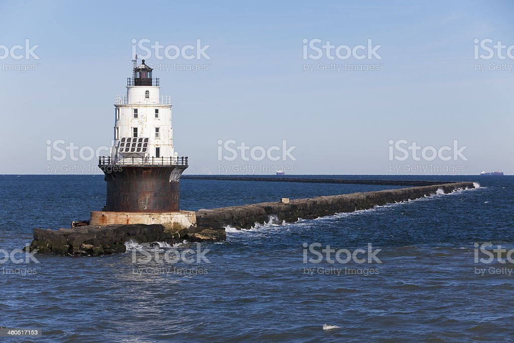 Stone walkway to Harbor Refuge Lighthouse on the water stock photo