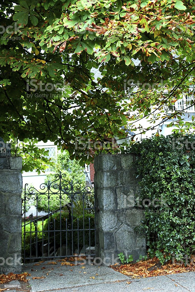 Stone wall and garden gate with trees royalty-free stock photo