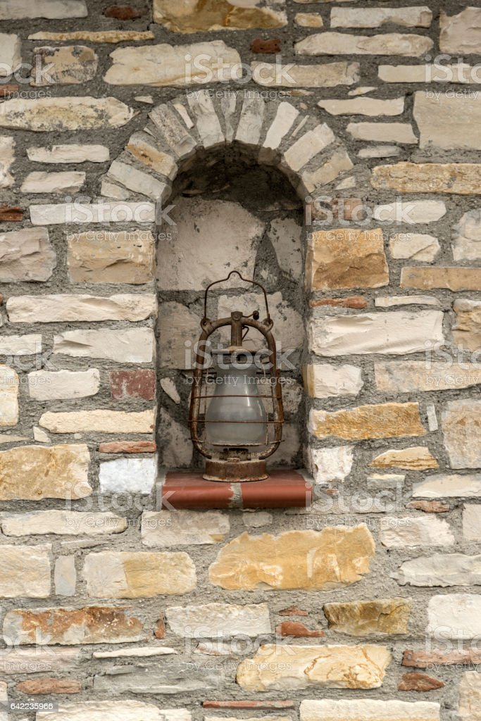 Stone wall and old oil lamp stock photo