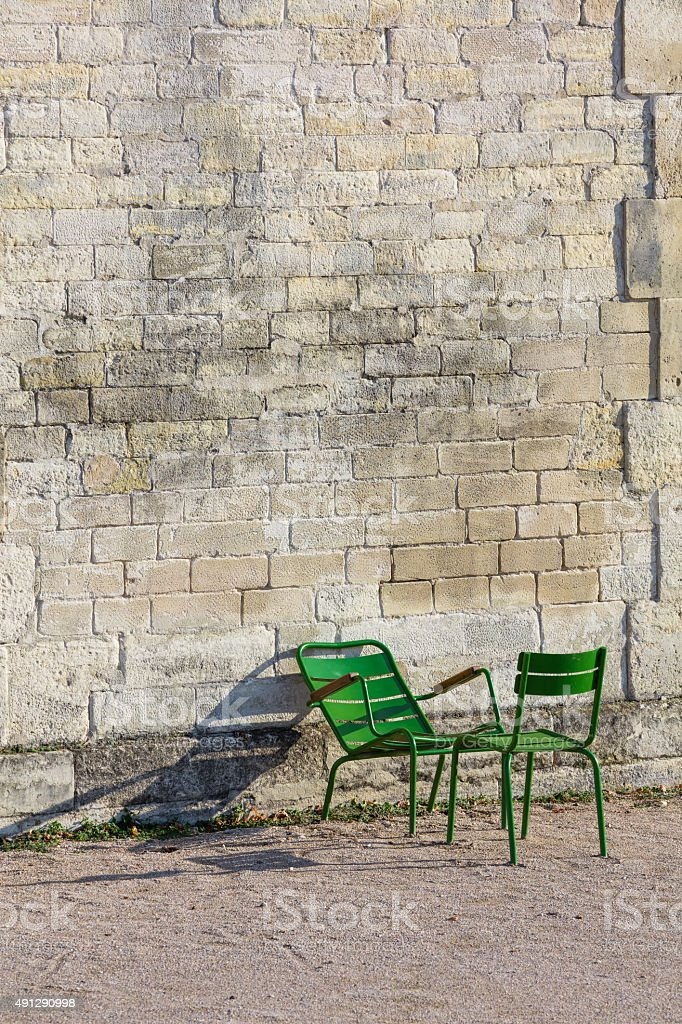 Stone wall and two green chairs in Tuileries Garden (Vertical) royalty-free stock photo