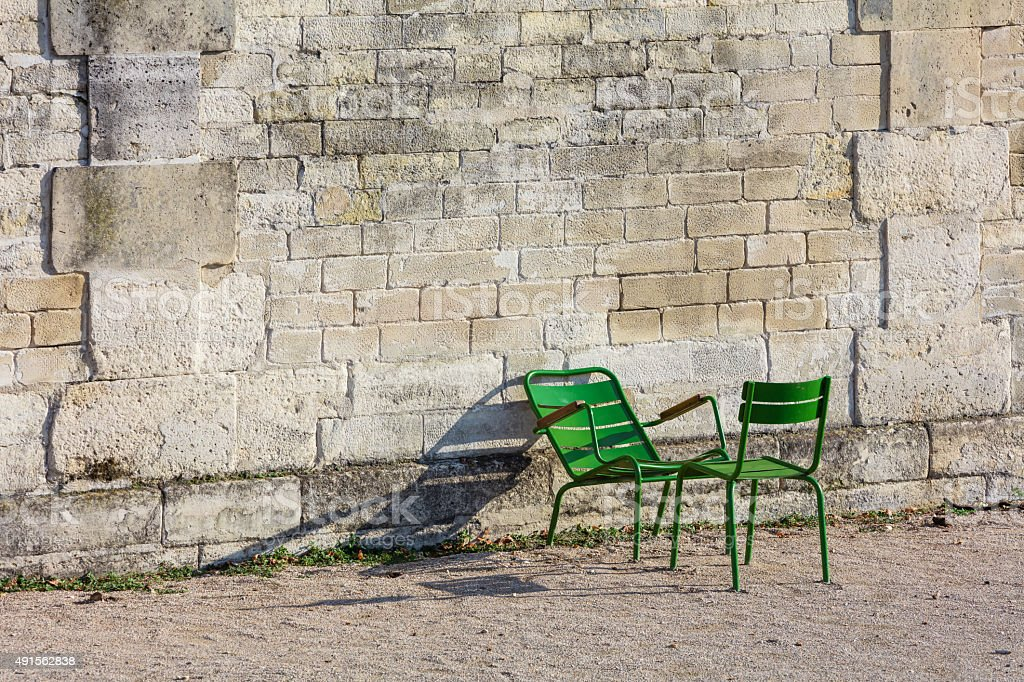 Stone wall and two green chairs in Tuileries Garden (Horizontal) royalty-free stock photo