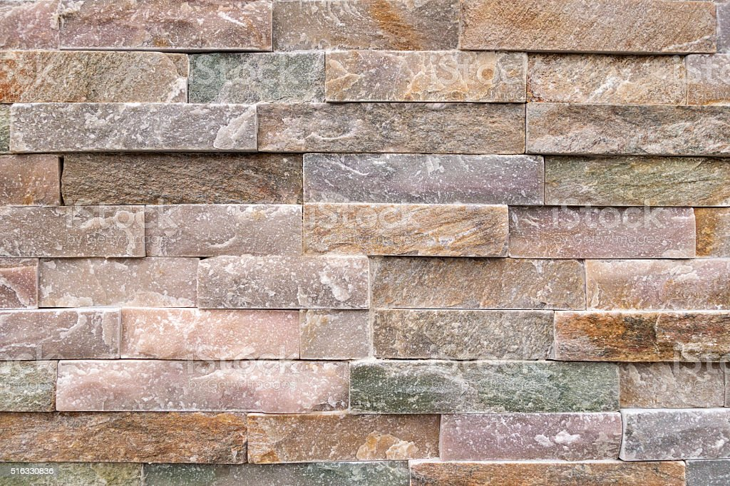 Stone wall of pastel-colored facing stones stock photo