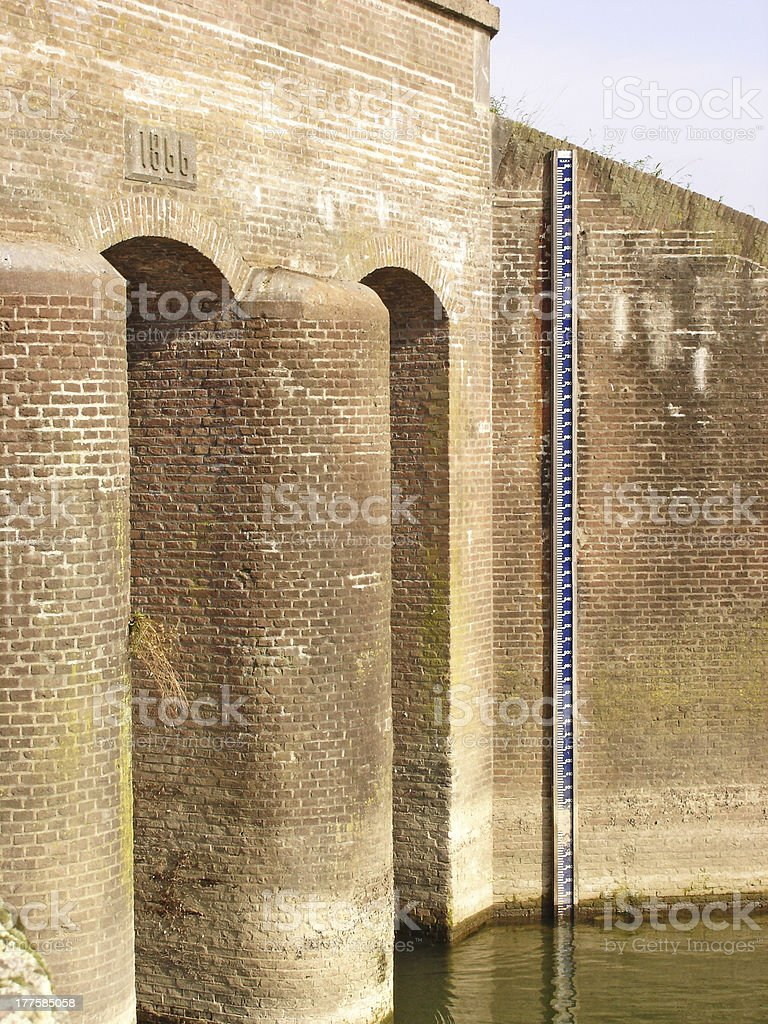 Stone wall of river inlet with gauge stock photo