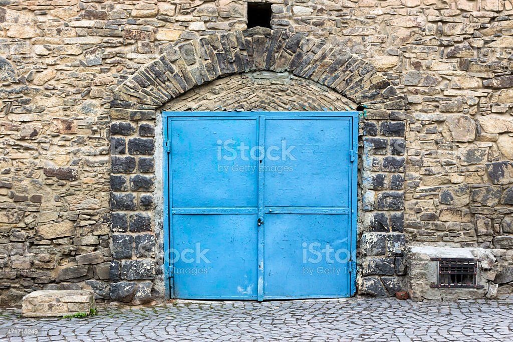stone wall with blue door royalty-free stock photo