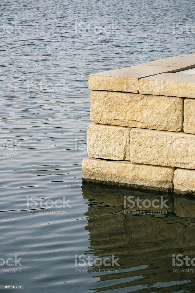 Stone wall with reflection on lake. royalty-free stock photo