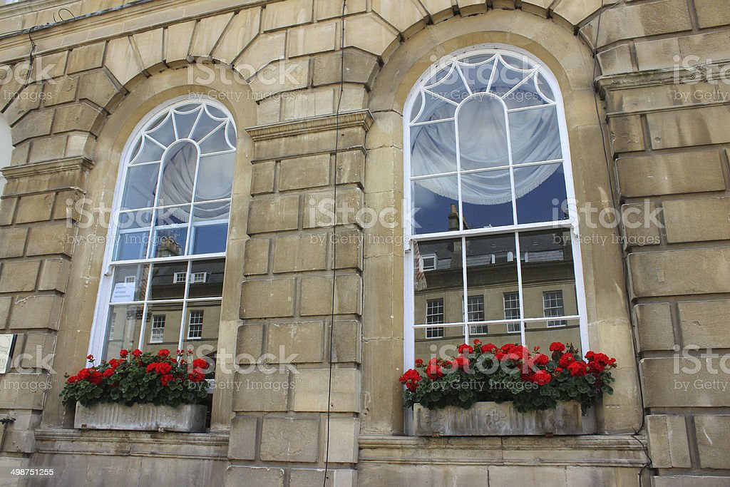 Stone window boxes with red flowers (geraniums / pelargoniums), Georgian house stock photo