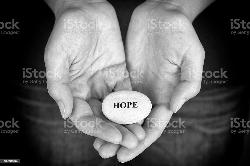 Stone with the word Hope in the woman's palms stock photo
