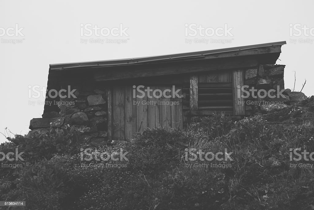 Stone wood shed in hillside from front black and white stock photo