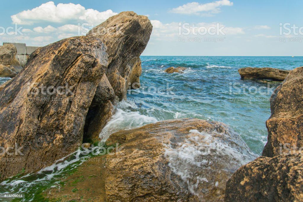 Stones at black sea shoreline above water stock photo