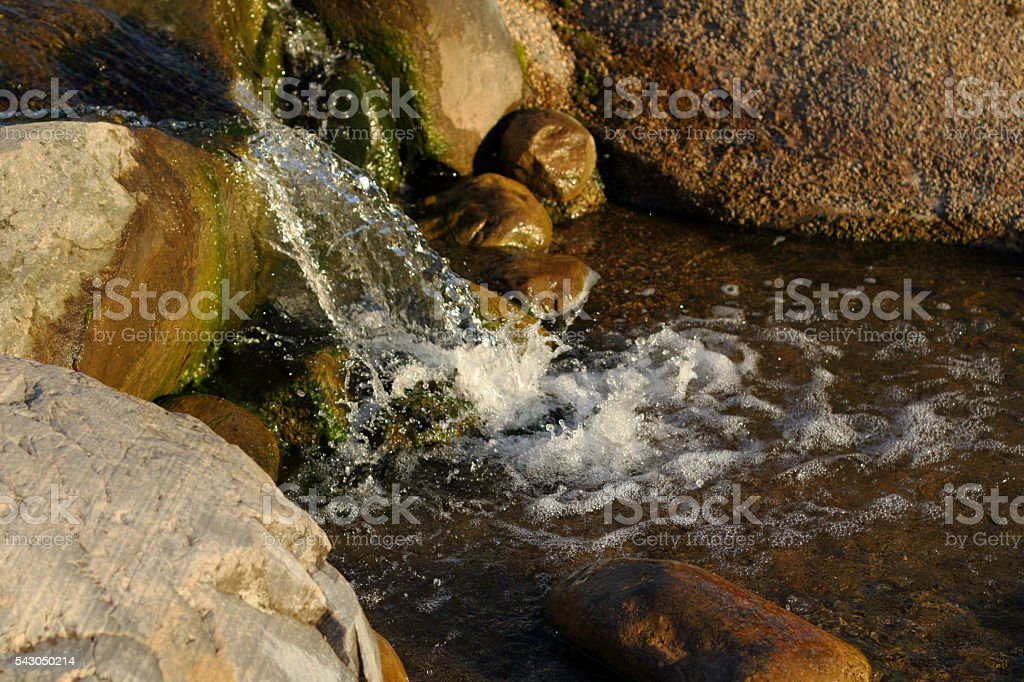 Stones in stream with smooth flowing water stock photo