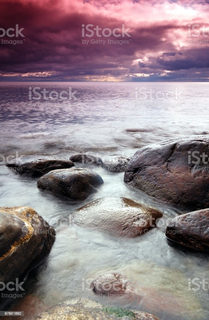 Stones in the blue sea with super red sunrise stock photo