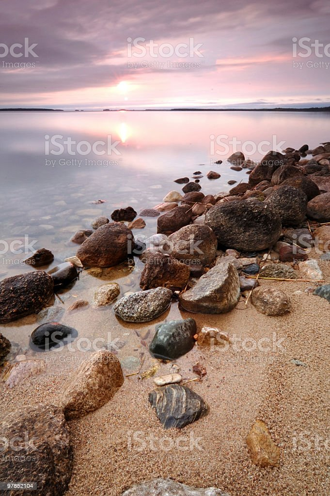 Stones in the lake with sunset and clouds stock photo