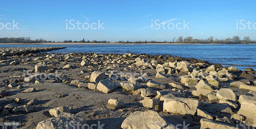Stones on a beach along a sunny river stock photo