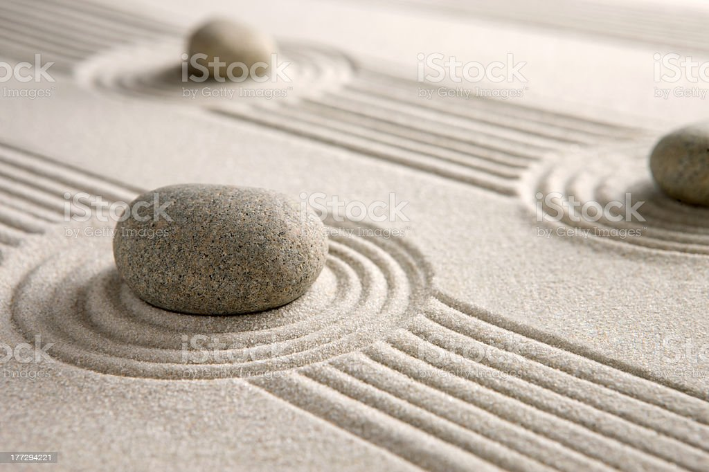 Stones on a neatly raked mini Zen garden stock photo